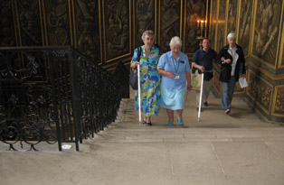 A room describer and some visitors walk up The King's Staircase