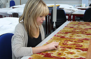 A conservator working on Queen Anne's bed
