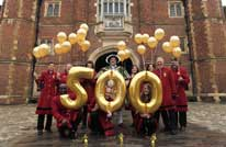 Henry VIII character actor and staff hold up balloons to celebrate the 500 year anniversary