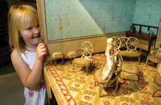 A child peeps round the edge of the dolls house