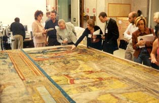 A team studying a tapestry