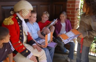 Kids with costumed character as George III on bench at Kew Palace