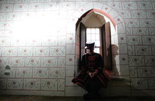 A Yeoman Warder sitting on a window ledge