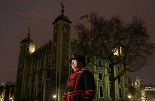 A Yeoman Warder standing in front of the White Tower at night