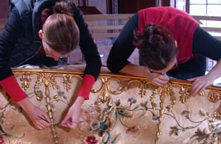 Conservators working on a bed dome